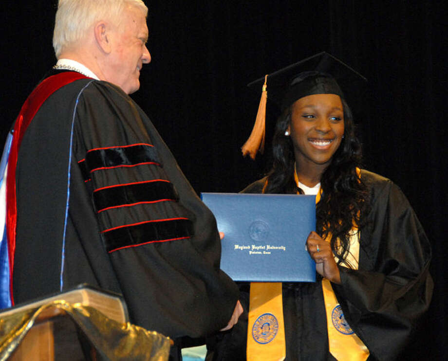 Jonathan Petty/Wayland Baptist UniversityJanelle Durrough, a graduating senior from Altus, Okla., receives her diploma from Dr. Paul Armes during Saturday's graduation. Later that day she wed classmate Lorenzo Dolphus of Houston.
