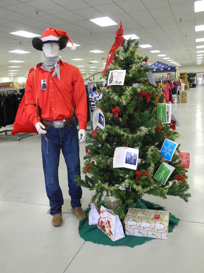 Visitors to Gebo's at 2803 Olton Road are greeted by Santa Tex standing next to the Paws Pet adoption tree. Visitors can take a pet card from the tree and visit Paws Pet Adoption of Plainview, 500 S.W. 3rd Street, or leave gifts for the shelter under the tree. Photo: Gail M. Williams | Plainview Herald