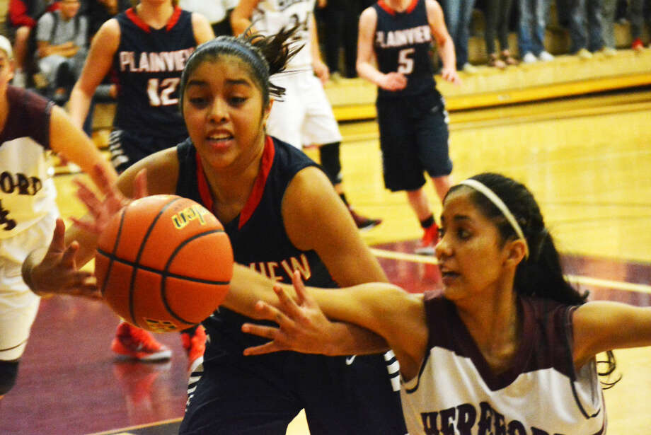 Plainview's Brittany Rincon (left) battles a Hereford player for possession of the basketball during a game in Hereford Tuesday night. The Lady Bulldogs fell to the Lady Whitefaces, 50-41. Photo: Doug McDonough/Plainview Herald