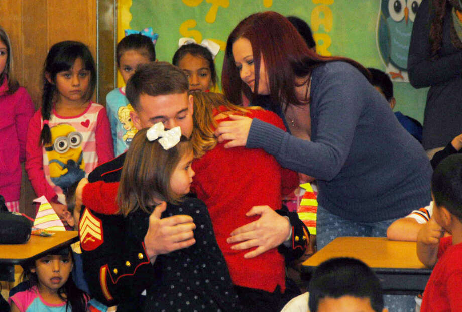 It was a tearful homecoming Wednesday as Marine Jake Churchwell surprised daughters Sleighten and Cadence during lunch at Edgemere Elementary school. Photo: Homer Marquez/Plainview Herald