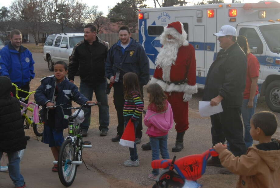 Terry Timms (right), Santa, Hale Center EMS director Matt Carter, Bill Ayers and EMT-I Colt Birdwell pass out toys during the ninth annual Santa Red and Blue toy drive Monday. Photo: Homer Marquez/Plainview Herald