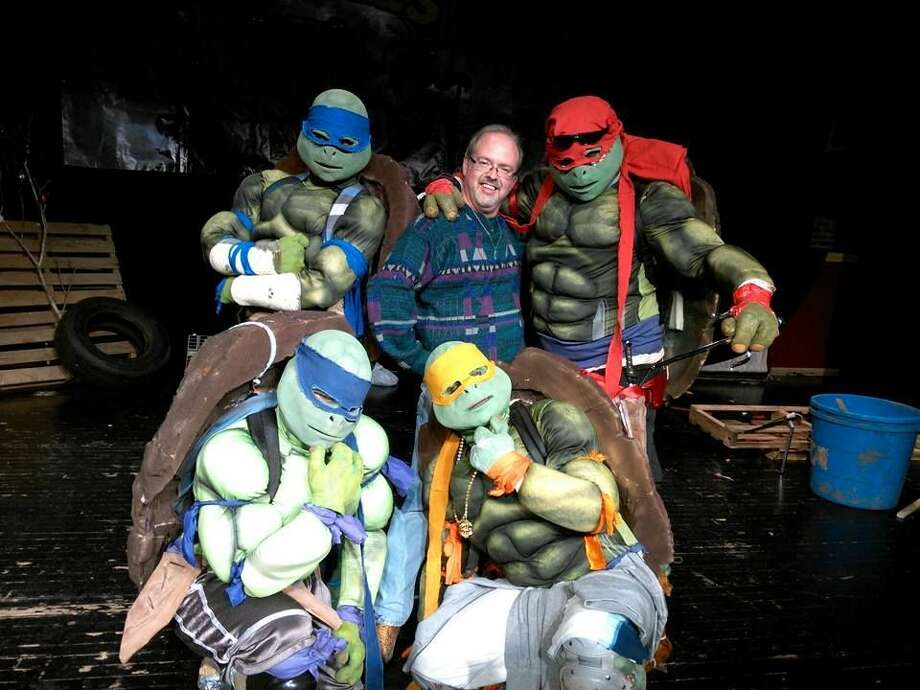 Courtesy Photo Shane Harrell is surrounded by Ninja Turtles last Saturday while on stage at the Fair Theatre.
