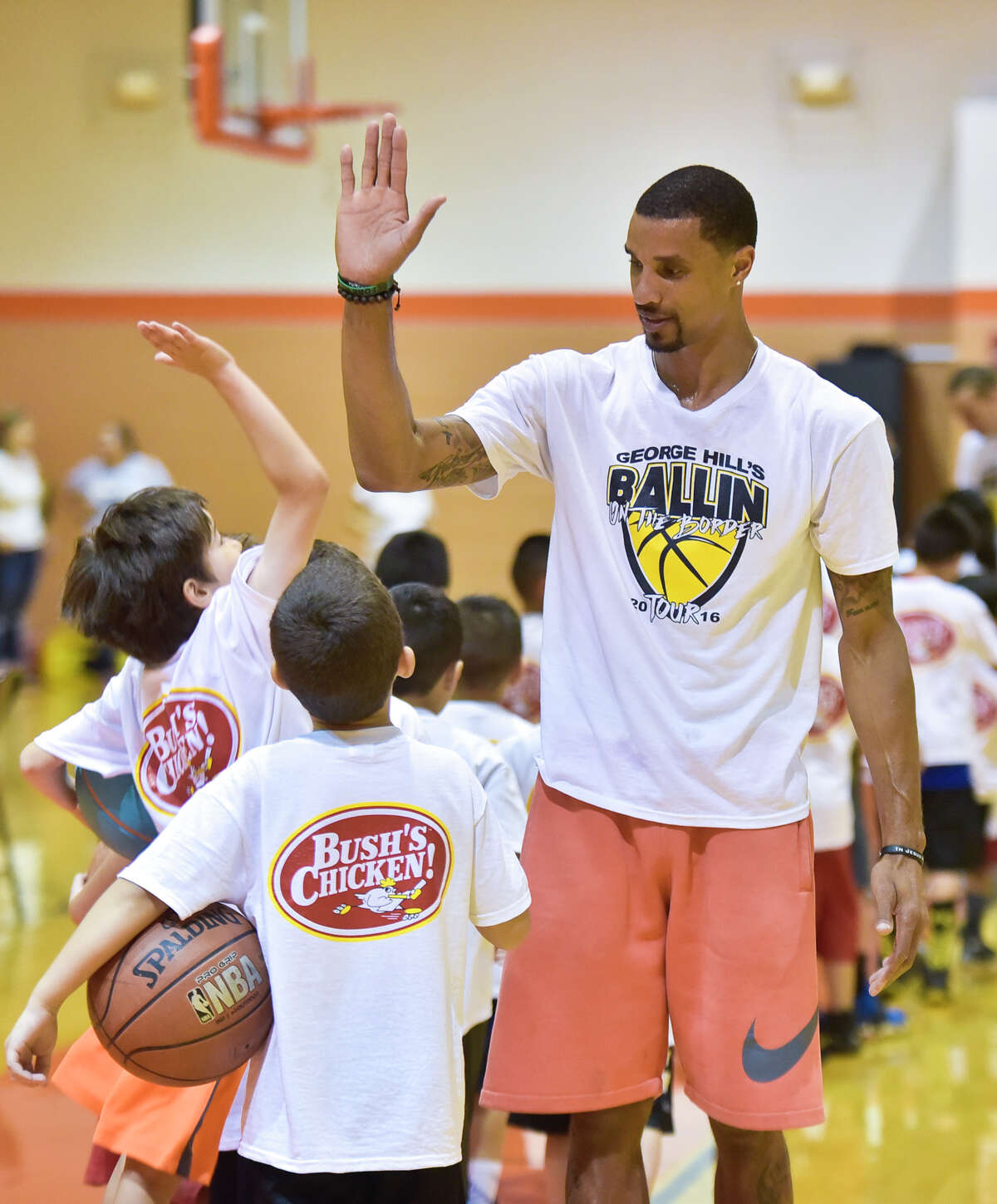 George Hill gives high fives to the kids in attendance during George Hill's Ballin' On The Border Basketball Camp at United High School on Monday afternoon.