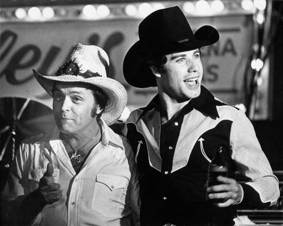 """Mickey Gilley, left, and John Travolta, who played Bud in the movie, whoop it up at a Houston movie premiere party for """"Urban Cowboy"""" at Gilley's. Photo: Larry Reese, HC Staff / Houston Chronicle"""