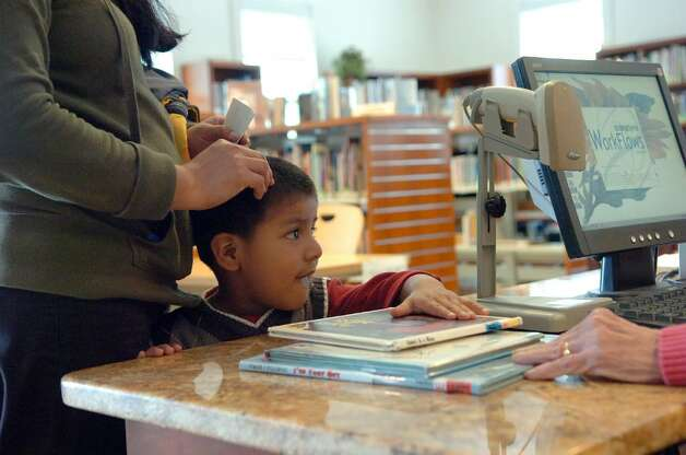 Apollo Garcia, 3, checks out a few books at Stamford Library's Weed Memorial & Hollander Branch Tuesday afternoon April 27, 2010. City lawmakers are pressuring the Board of Finance to return $1.2 million to the budget to prevent library branch closures and reduced hours but Board of Finance chair Joe Tarzia said the city charter prohibits such a move. Photo: Keelin Daly / Stamford Advocate