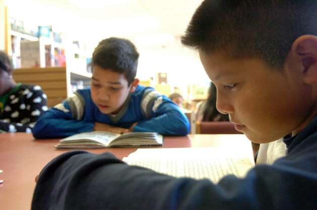 Eric Vasquez, 10, right, and Alex Cuellar, 9, study with the CTE After School Academy's fourth and fifth grade reading club at Stamford Library's South End Branch Tuesday afternoon April 27, 2010.  City lawmakers are pressuring the Board of Finance to return $1.2 million to the budget to prevent library branch closures and reduced hours but Board of Finance chair Joe Tarzia said the city charter prohibits such a move. Photo: Keelin Daly / Stamford Advocate
