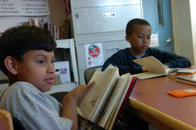 Emerson Curuz Gonzales, 9, and Gianni Lorquet, 9, study with the CTE After School Academy's fourth and fifth grade reading club at Stamford Library's South End Branch Tuesday afternoon April 27, 2010.  City lawmakers are pressuring the Board of Finance to return $1.2 million to the budget to prevent library branch closures and reduced hours but Board of Finance chair Joe Tarzia said the city charter prohibits such a move. Photo: Keelin Daly / Stamford Advocate