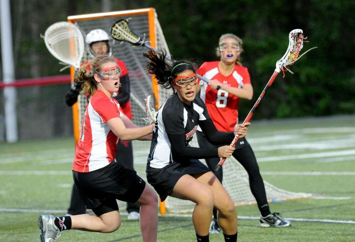 New Canaan's Anjalie Christie spins past Greenwich's Shannon Colligan as Tori Dunster guards the goal as New Canaan hosts Greenwich in a girls lacrosse game at Dunning Field Tuesday evening April 27, 2010. New Canaan won the match 16-5.