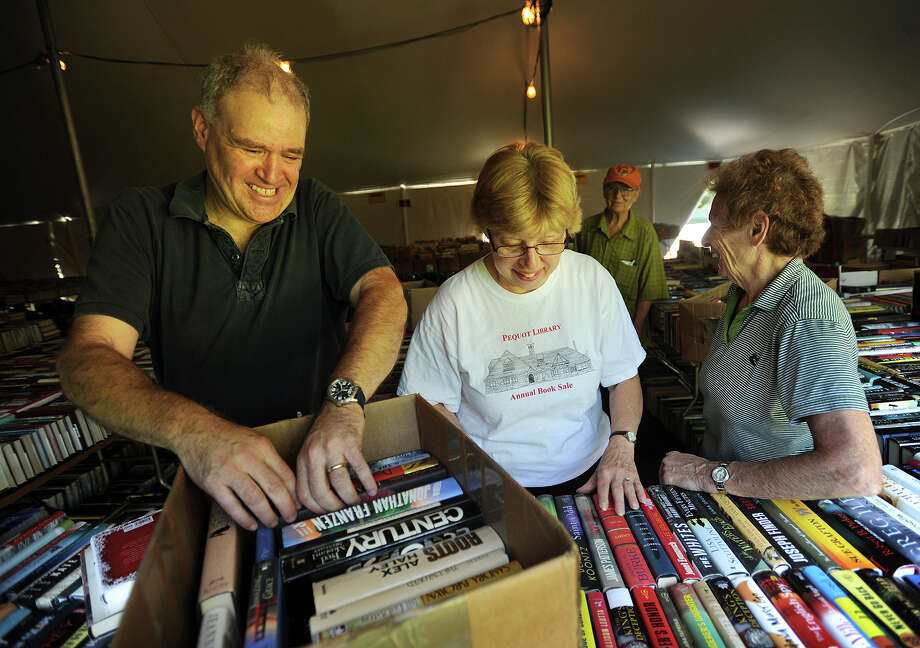 From left, book sale Chairman Doug Fried and volunteers Roberta Gagne, of Fairfield, Paige Gillies, of Easton, and Sandy Zera, of Fairfield, put out a box of books of the over140 thousand items for sale at the 56th Annual Pequot Library Book Sale in the Southport section of Fairfield on Tuesday. The sale runs from Friday until July 26. Hours Friday are 9 a.m. to 7 pm, Saturday through Monday 9 am-6 pm, and Tuesday 9 am-2 pm. Photo: Brian A. Pounds / Hearst Connecticut Media / Connecticut Post