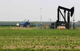 A tractor shares farmland with an oil pump in a field on March 5, 2014, near Shafter, Calif. Though there could be 15 billion barrels of oil trapped in the Monterey Shale in Kern County, getting to them through California's complicated, earthquake-altered geology could be a prohibitively expensive undertaking. (Brian van der Brug/Los Angeles Times/MCT)