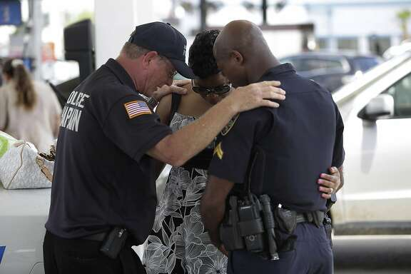 BATON ROUGE, LA - JULY 19: Millville, New Jersey police chaplain Bob Ossler (L) prays with Baton Rouge Police Department Corporal Trina Dorsey (C) and her brother Corporal Joseph Keller near a makeshift memorial for three police officers on July 19, 2016 in Baton Rouge, Louisiana. Three police officers were killed and several others wounded along Airline Highway Sunday when Gavin Long, who traveled from Kansas City, Missouri, ambushed the law enforcement officers. (Photo by Joshua Lott/Getty Images)