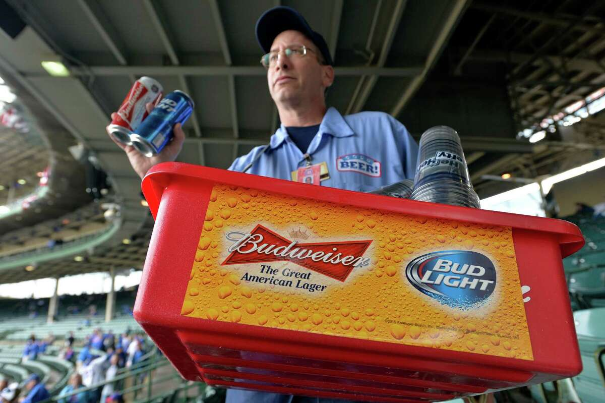 FILE - In this Tuesday, Oct. 13, 2015, file photo, a beer vender holds up Budweiser and Bud Light at Wrigley Field before Game 4 in baseball's National League Division Series between the Chicago Cubs and the St. Louis Cardinals in Chicago. Anheuser-Busch InBev, the world's largest beer maker, announced Wednesday, July 20, 2016, that it has reached an agreement with the Justice Department clearing the way for U.S. approval of its acquisition of SABMiller. (AP Photo/Paul Beaty, File) ORG XMIT: NYBZ312