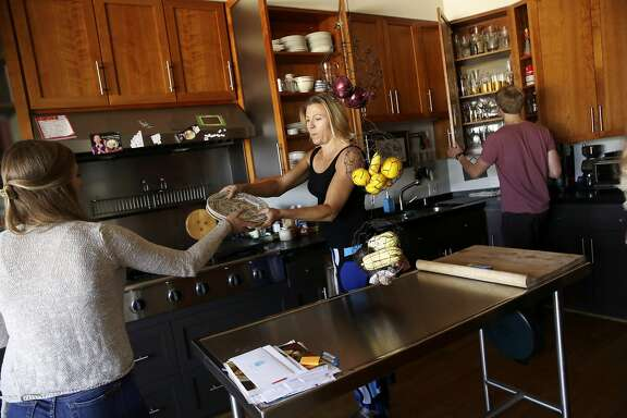 "Colleen Kavanagh (center) hands plates to her daughter Kelsey Puknys (left), 15 while in the kitchen with her son Liam Puknys (right), 18, in their home on Monday, May 16, 2016 in San Francisco, California.  Erik Puknys and Colleen Kavanagh have rented out their Cole Valley house via Airbnb a grand total of seven nights and the city has required them to fill out a form detailing every item in their home as part of a move to impose business tax on these items. Moreover, the form the city sent said not to itemize things from ""any unit in which you live"" - and they live in their house."