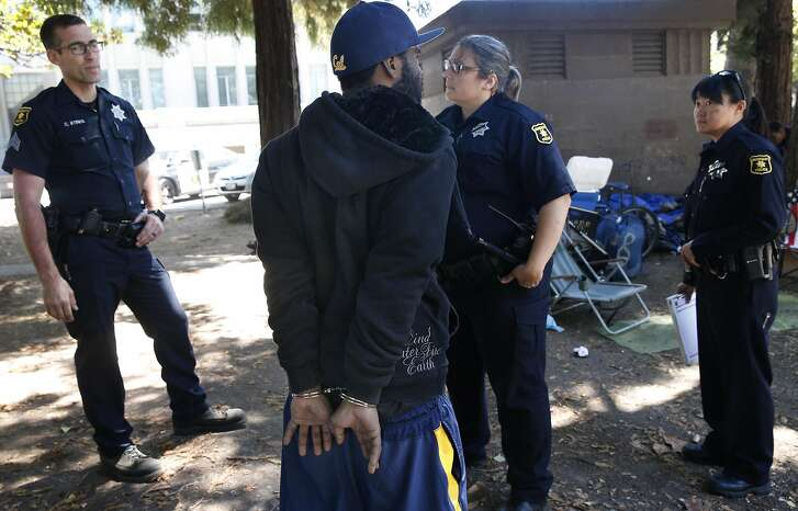 Police officers arrest a man on suspicion of robbery at Civic Center Park in Berkeley, Calif. on Wednesday, July 20, 2016. Police officers are more cautious while on patrol following the recent ambush shooting deaths of officers in Dallas and Baton Rouge.