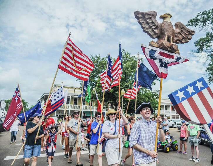 Jason Bouldin leads those with Revolutionary War-era flags during a July 4th parade.