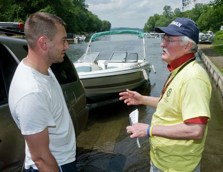 Steven DaSilva of Danbury listens to George Linkletter, a trained invasive investigator, talk about zebra mussels at Lattins Cove boat launch. Saturday, May 28, 2011 Photo: Scott Mullin / ST / The News-Times Freelance