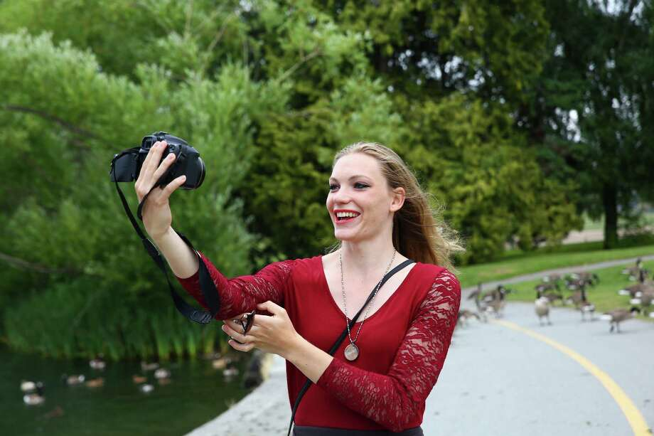 Local musician Claire Michelle, 23, makes a vlog as she walks around Green Lake, June 23, 2016.  Claire began vlogging when she moved to Seattle from Michigan two years ago, this is also when she began her transition from male to female.  Like many young trans people, Claire found community, support and information on the internet.  From her small hometown in Michigan, she used Reddit to connect with a wider world of people going through the same things as her. She began vlogging about her own transition, and now her life in Seattle and her music, as a way to give back to that community. Photo: GENNA MARTIN, SEATTLEPI.COM / SEATTLEPI.COM