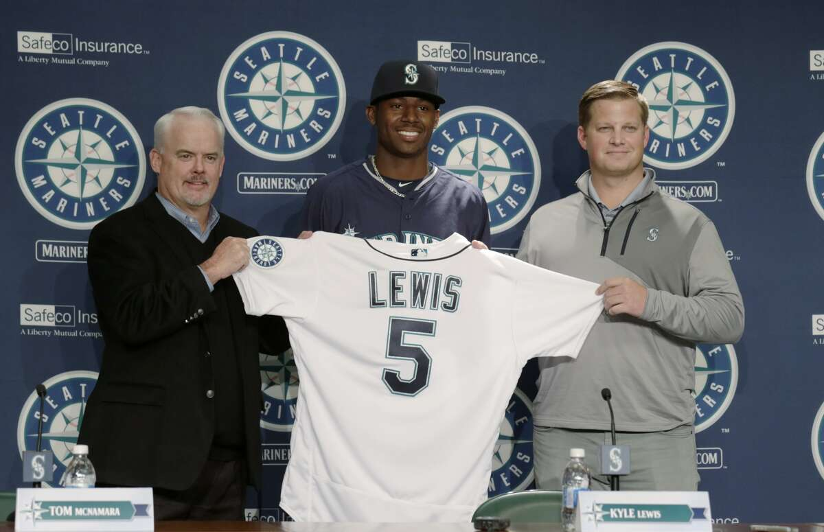 Seattle Mariners first-round draft pick Kyle Lewis holds up his jersey with Tom McNamara, director of amateur scouting, left, and scout John Wiedenbauer, right, during a news conference Saturday, June 11, 2016, in Seattle. (AP Photo/John Froschauer)