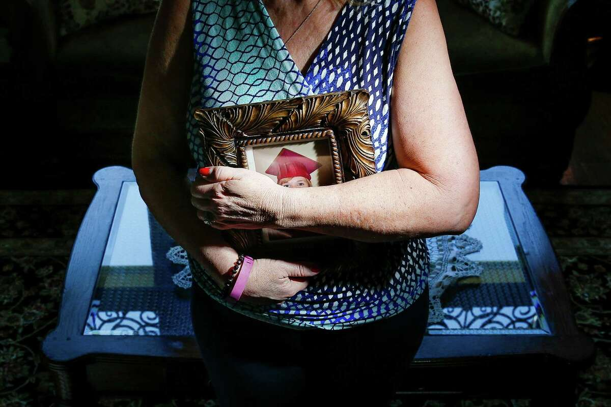 A mother, who wished not to be identified, stands with a picture of her mentally ill daughter, who was ordered to jail after she had a psychological breakdown while testifying against her attacker.