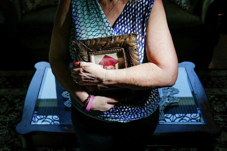 A mother, who wished not to be identified, stands with a picture of her mentally ill daughter, who was ordered to jail after she had a psychological breakdown while testifying against her attacker.  Photo: Michael Ciaglo, Staff / © 2016  Houston Chronicle