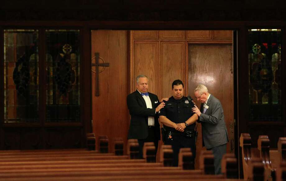 Tripp Stuart, left, and Ken Finch pray for San Antonio Police Detective George Silva during a Citywide Prayer Service for First Responders and Unity at First Presbyterian Church, Wednesday, July 20, 2016. Members from different churches offered their prayers for the law enforcement community and the City of San Antonio. Photo: Jerry Lara, San Antonio Express-News / © 2016 San Antonio Express-News