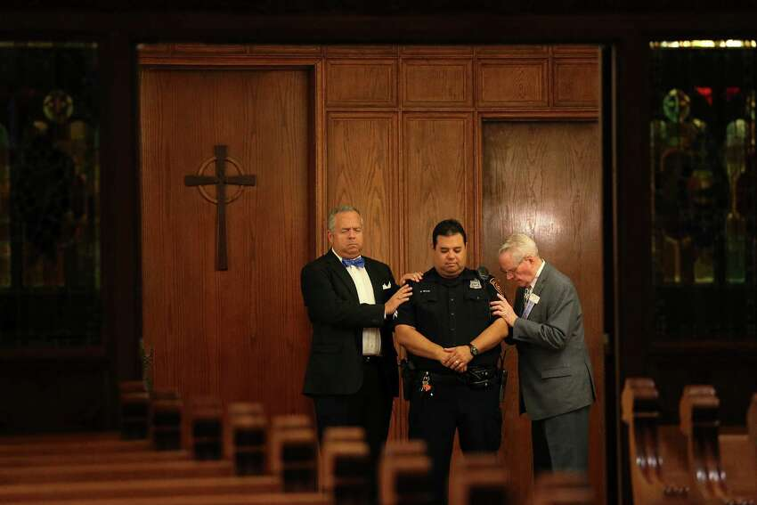 Tripp Stuart, left, and Ken Finch pray for San Antonio Police Detective George Silva during a Citywide Prayer Service for First Responders and Unity at First Presbyterian Church, Wednesday, July 20, 2016. Members from different churches offered their prayers for the law enforcement community and the City of San Antonio.