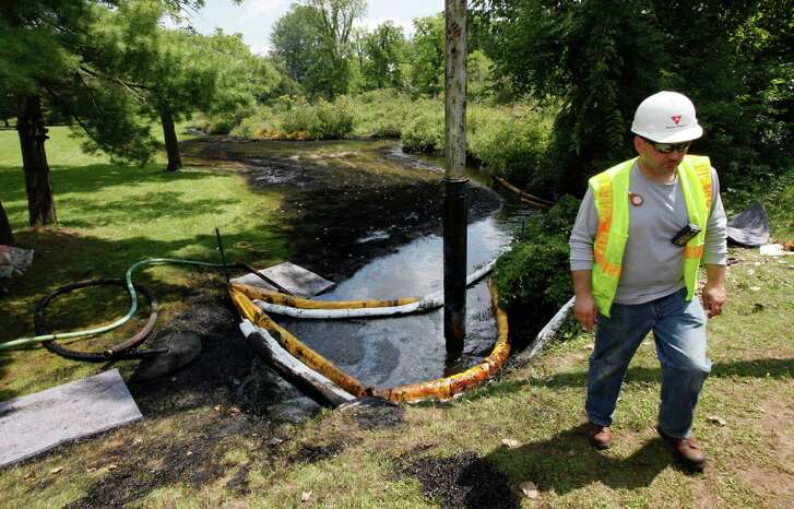 FILE - In this July 29, 2010 file photo, a worker monitors the water in Talmadge Creek in Marshall Township, Mich., near the Kalamazoo River as oil from a ruptured pipeline, owned by Enbridge Inc, is vacuumed out the water. Enbridge Energy Partners will pay a $61 million penalty for the costliest inland oil spill in U.S. history under an agreement with federal officials. The U.S. Environmental Protection Agency and the Department of Justice announced the settlement Wednesday, July 20, 2016. It involves a 2010 pipeline rupture near Marshall that released an estimated 843,000 gallons of crude oil. A nearly 40-mile stretch of the Kalamazoo River was polluted as shoreline residents fled their homes.(AP Photo/Paul Sancya, File)