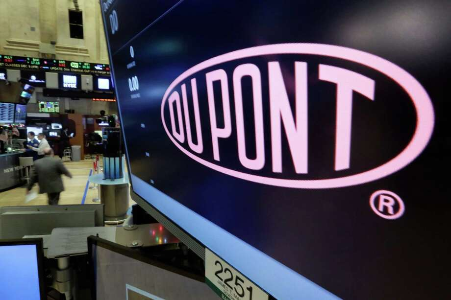 FILE - In this Dec. 9, 2015 file photo, the company name of Dupont appears above its trading post on the floor of the New York Stock Exchange. Shareholders for agriculture and chemicals companies DuPont and Dow Chemical have approved their merger, as well as a subsequent plan that will break up the century-old companies into three parts. Combined, Dow and DuPont will be the second-largest chemicals company in the world. Within two years, they plan to split into three separate publicly traded companies focused on agriculture, material science and specialty products. (AP Photo/Richard Drew, File) Photo: Richard Drew, STF / Copyright 2016 The Associated Press. All rights reserved. This material may not be published, broadcast, rewritten or redistribu
