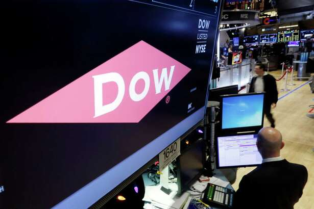 FILE - In this Wednesday, Dec. 9, 2015, file photo, the company name of Dow appears above its trading post on the floor of the New York Stock Exchange. Shareholders for agriculture and chemicals companies DuPont and Dow Chemical have approved their merger, as well as a subsequent plan that will break up the century-old companies into three parts. Within two years, they plan to split into three separate publicly traded companies focused on agriculture, material science and specialty products. (AP Photo/Richard Drew, File)