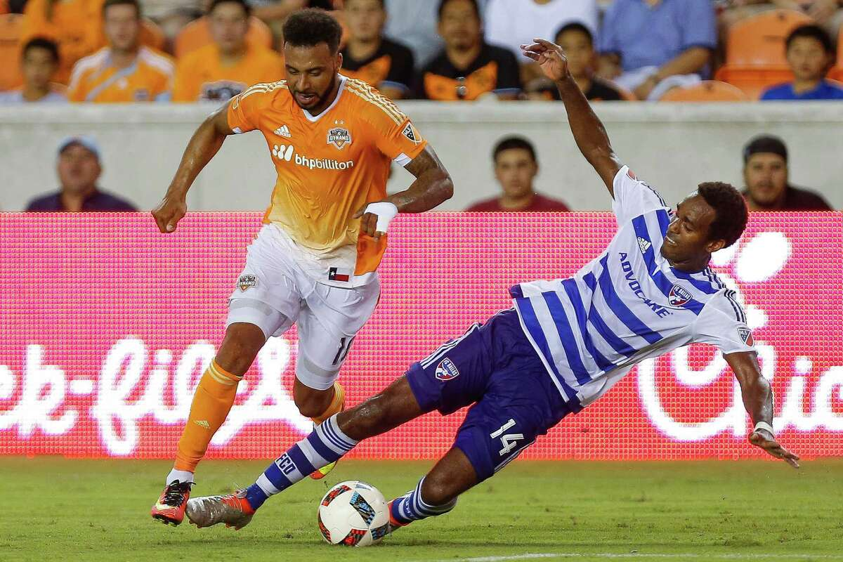 FC Dallas forward Atiba Harris, right, gets a bit too aggressive trying to stop Giles Barnes and receives a yellow card for tripping the Dynamo forward.