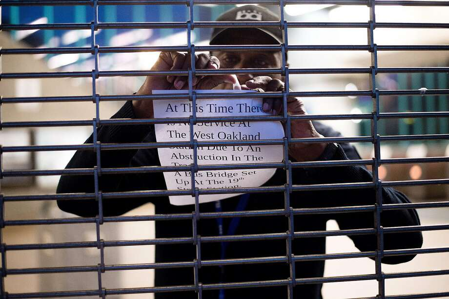 A BART worker hangs a closure notice on a gate at the West Oakland station on Wednesday, July 20, 2016, in Oakland, Calif. A truck that crashed through a barrier and onto the BART tracks in West Oakland shut down transbay service for about 90 minutes. Photo: Noah Berger, Special To The Chronicle