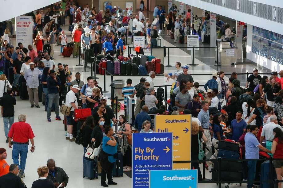 Southwest Airlines passengers line up at the ticketing and check-in counters at Hobby Airport on Thursday, July 21, 2016, in Houston. A technology problem at Southwest caused delays and cancelled flights throughout the airline's system. ( Brett Coomer / Houston Chronicle )