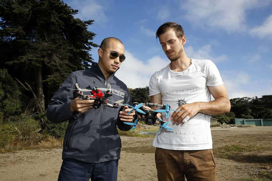 Mark Nano (left) and Colby Curtola compare drone designs before sending the crafts for flights at Golden Gate Park. Photo: Connor Radnovich, The Chronicle