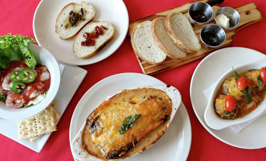 An assortment of dishes: (from left) shrimp cocktail, housemade bread with jalapeño and chile piquín jelly, bread presentation, stuffed champiñones and eggplant-tomato lasagna. Photo: Edward A. Ornelas /San Antonio Express-News / © 2016 San Antonio Express-News