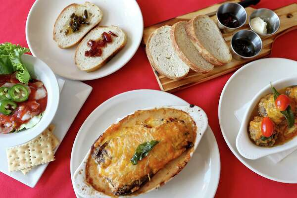 An assortment of dishes: (from left) shrimp cocktail, housemade bread with jalapeño and chile piquín jelly, bread presentation, stuffed champiñones and eggplant-tomato lasagna.