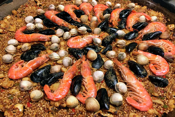 A Catalonia-style seafood paella is being prepared by tourists at cooking class offered by cooking school Cook and Taste in Barcelona, Spain.