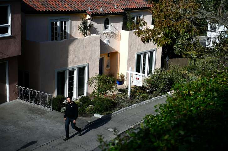 A passerby walks by a home for sale on Magellan Ave on Wednesday, July 20, 2016 in San Francisco, California.
