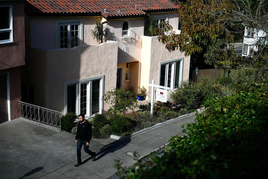 A passerby walks by a home for sale in San Francisco. Only 15 percent of households in the city can afford a median-price home, which averages $1,610,000, according to a new survey. Photo: Michael Noble Jr. / The Chronicle 2016