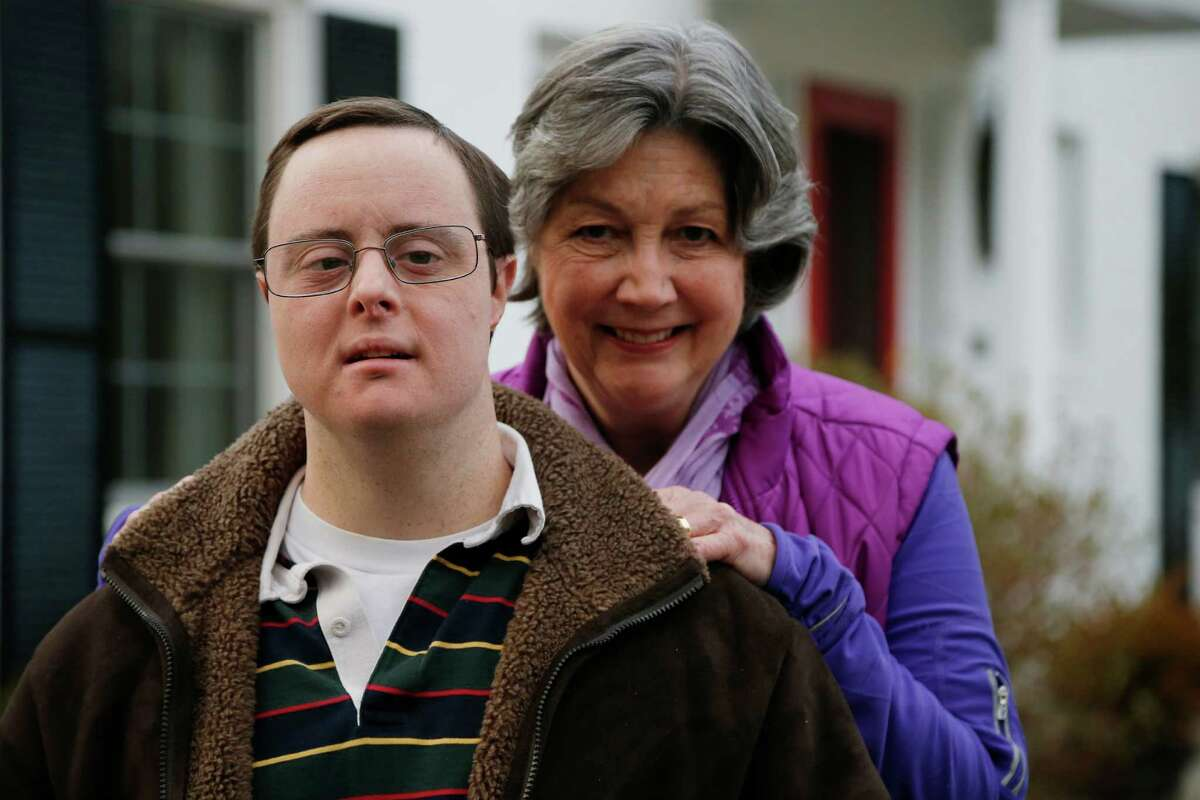 This photo taken Feb. 10, 2014 show Matthew McMeekin, along with his mother, Bebe McMeekin, posing for a photograph at their home in Bethesda, Md. Most Americans with intellectual or developmental disabilities remain shut out of the workforce, despite changing attitudes and billions spent on government programs to help them. Even when they find work, it's often part time, in a dead-end job or for pay well below the minimum wage. McMeekin, 35, of Bethesda, Md., has spent 14 years working at Rehabilitation Opportunities Inc., a nonprofit sheltered workshop where he and other disabled workers are bused each workday to stuff envelopes, collate files or shrink-wrap products _ all for far less than the state minimum wage of $8.25 an hour. (AP Photo/Charles Dharapak)