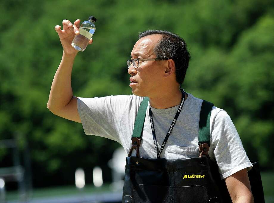 Edwin Wong, a biology professor at Western Connecticut State University, takes a water sample from Candlewood Lake at Lynn Deming Park in New Milford. The sample will be tested for the presence of toxic blue-green algae. Photo: Carol Kaliff / Hearst Connecticut Media / The News-Times