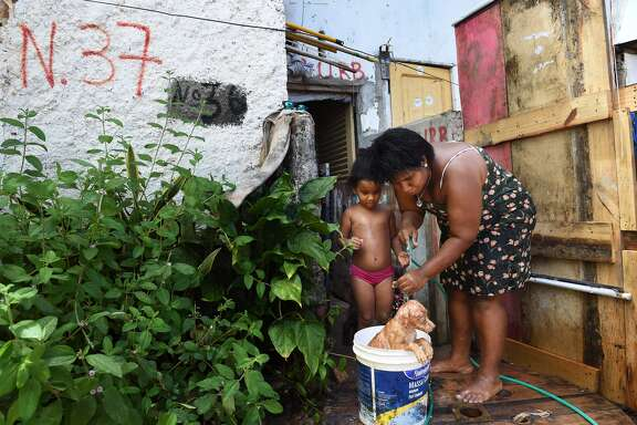 Jamilly Vitoria Santos da Silva, center, stands next to her mother, Rebeca Arruda as they wash a dog in a bucket in a favela as members of the Brazilian military along with health care workers to talk to residents about the threat of Zika virus.