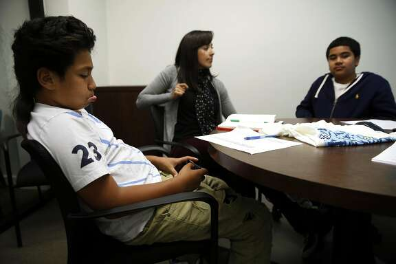 CFO Jahziah Talatoa (left), 12, plays a game on his phone while Veronica Frieling and CFO Jahem Maua, 13, talk during a business meeting at Umpqua Bank in San Francisco, California, on Tuesday, July 19, 2016.