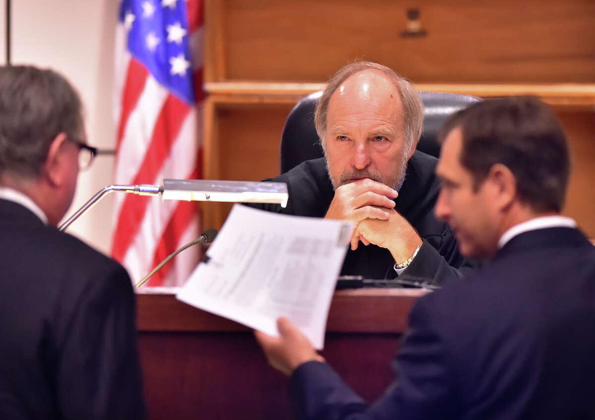 Judge Sid Harle of the 226th State District Courtlistens to defense attorney Richard Langlois (left) and prosecutor Geoff Barr during the capital murder trial of Dominique Green Wednesday.