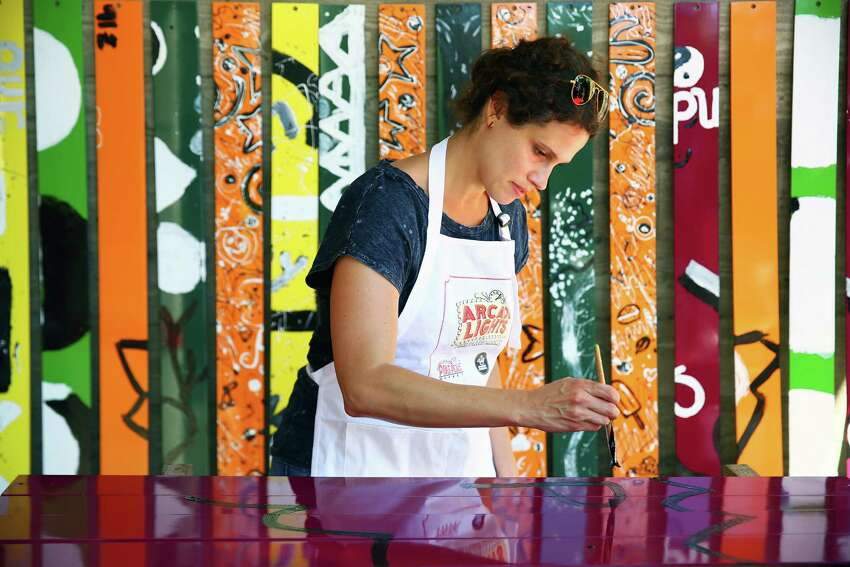 Katy Waggoner paints brightly colored panels at a Community Collaborative Art Pop-Up event at Pike Place Market, July 21, 2016. From July 20-24, local artist John Fleming is hosting painting sessions. The panels will later be installed as a permanent art fixture on Western Avenue across from the new MarketFront.