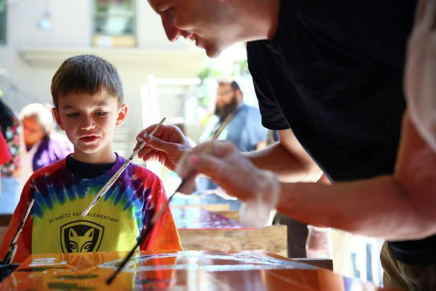 Leo Bronk, 8, watches as Todd Bronk, right, paints brightly colored panels.