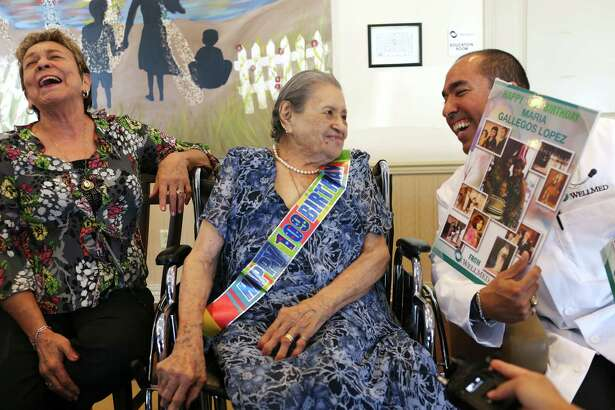 Dr. Richard Prezas, right, presents Maria Gallegos Lopez with a photo collage in celebration of her 109th birthday at the WellMed Clinic at 4438 Centerview, Thursday, July 21, 2016. Gallego Lopez spent time with friends and family at the gathering. Grammy legend Flaco Jimenez showed up and help sing her birthday wishes. On the left is her daughter, Rosemary Galvan.