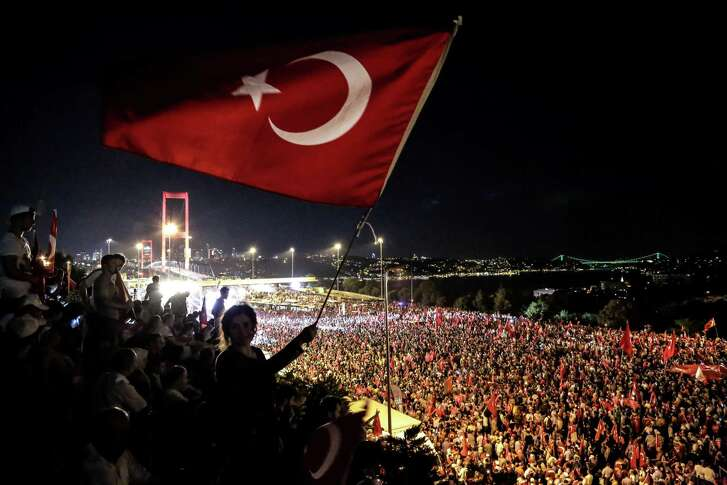Pro Erdogan supporters wave a Turkish national flag during a rally at Bosphorus bridge in Istanbul. Thousands of Turkish government supporters on Thursday streamed across one of the two bridges spanning the Bosphorus in Istanbul to protest against the coup that sought to unseat President Recep Tayyip Erdogan one week ago. (AFP/Getty Images)