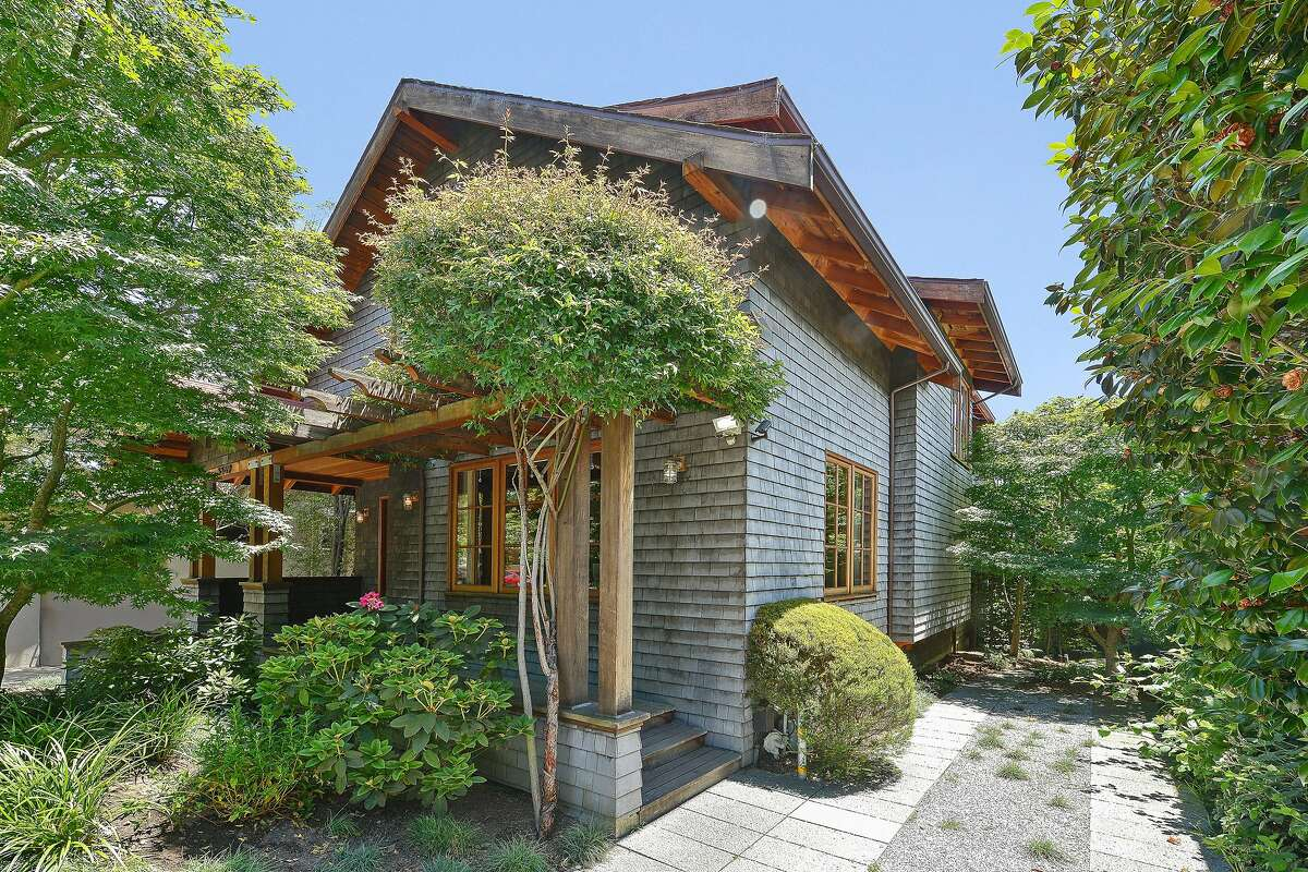 Overhanging eaves and wooden shingles form the facade of the Arts and Crafts style home.