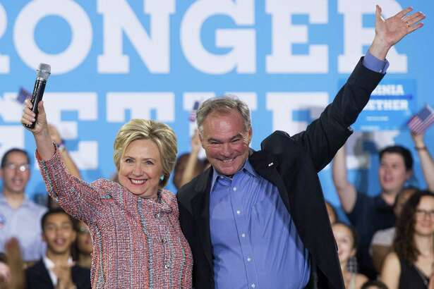 (FILES) This file photo taken on July 14, 2016 shows  US Democratic Presidential candidate Hillary Clinton and US Senator Tim Kaine, Democrat of Virginia, waving during a campaign rally at Ernst Community Cultural Center in Annandale, Virginia. Clinton is expected to reveal her vice presidential pick by July 23, when she campaigns in Florida. Kaine is mentioned first in virtually ever veepstakes discussion because he ticks so many boxes: strong foreign policy experience (he is on the armed services and foreign relations committees); loyal lawmaker from a battleground state; Spanish-speaker.  / AFP PHOTO / SAUL LOEBSAUL LOEB/AFP/Getty Images
