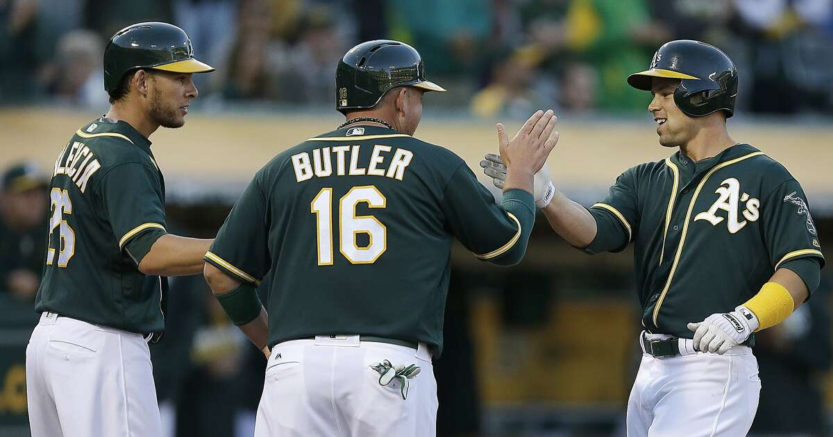 Oakland Athletics' Jake Smolinski, right, celebrates with Danny Valencia, left, and Billy Butler (16) after hitting a three run home run off Tampa Bay Rays' Matt Moore in the second inning of a baseball game Thursday, July 21, 2016, in Oakland, Calif. (AP Photo/Ben Margot)